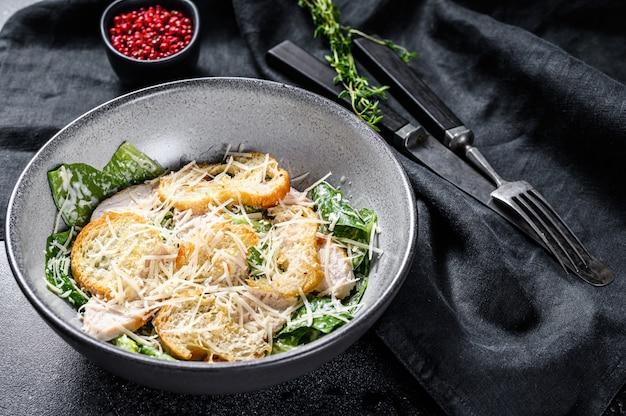 Salada caesar coberta com queijo parmesão, biscoitos costa. comida saudável. fundo preto. vista do topo