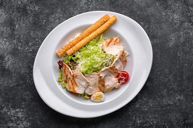 Salada caesar com carne de frango, alface, tomate, queijo e ovos, em um prato branco