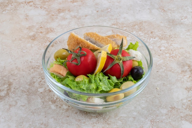 Salada caesar com ervas, legumes e nuggets de frango.