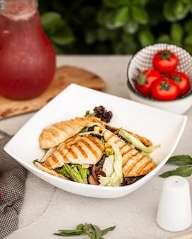 Salada caesar com fatias de filé de frango grelhado.