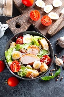 Salada caesar com frango defumado e parmesão em um prato em fundo escuro. vista do topo