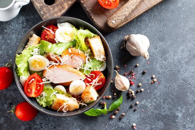 Salada caesar com frango defumado e parmesão em um prato em fundo escuro. vista superior, copie o espaço.