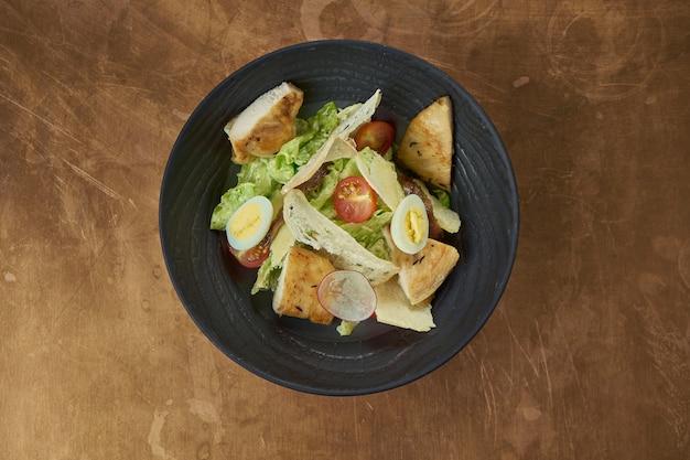 Salada caesar com frango e croutons em um prato preto. fundo de cobre
