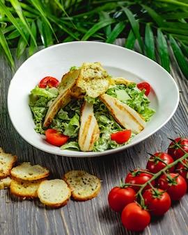 Salada caesar com frango e tomate cereja em um prato branco sobre uma mesa de madeira