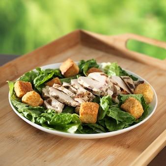 Salada caesar com frango grelhado na bandeja de madeira