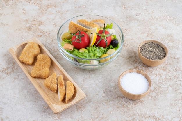 Salada caesar com nuggets de frango, ervas e tomate cereja.