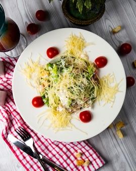 Salada caesar com parmesão picado e tomate cereja, vista superior.