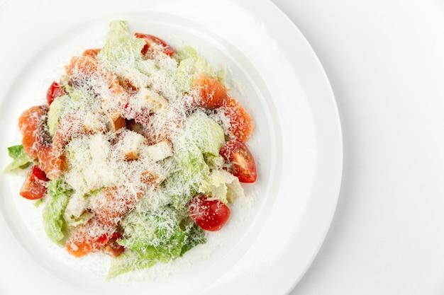 Salada caesar com peixe salgado em um prato branco. lanche festivo tradicional. fechar-se. fundo branco. espaço para texto.