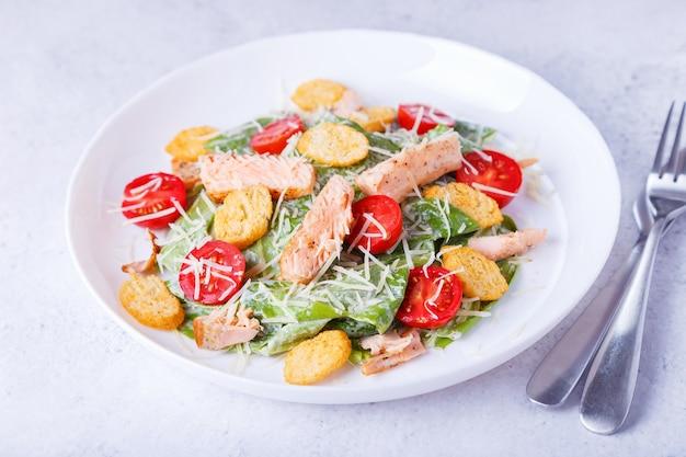 Salada caesar com peixe vermelho (salmão, truta), tomate cereja, croutons, queijo parmesão e alface romana. prato tradicional americano. close-up, foco seletivo.