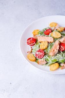 Salada caesar com peixe vermelho (salmão, truta), tomate cereja, croutons, queijo parmesão e alface romana. prato tradicional americano. copie o espaço. close-up, foco seletivo.