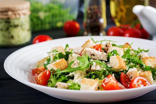 Salada caesar de frango grelhado saudável com tomate, queijo e pão torrado.