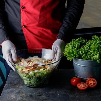 Salada caesar de vista lateral com tomate e alface e mão humana na mesa
