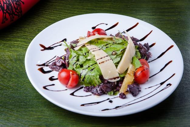Salada caesar decorada em um prato branco sobre uma mesa verde