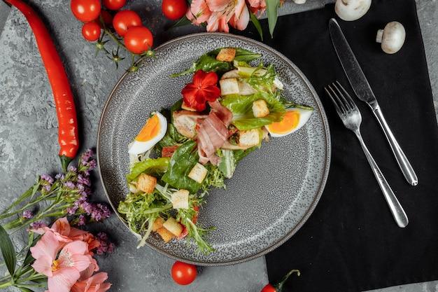 Salada caesar em prato cinza com decoração