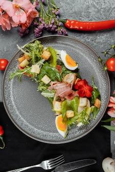 Salada caesar em um prato cinza com decoração e copyspace
