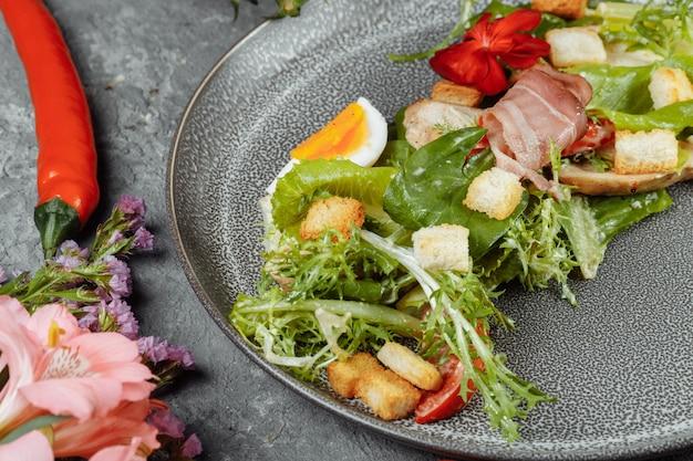 Salada caesar em um prato cinza com decoração e copyspace.