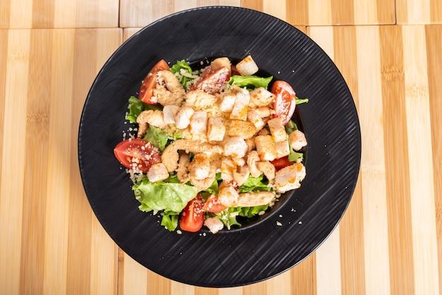 Salada caesar em uma placa preta, sobre um fundo de madeira. para qualquer propósito.
