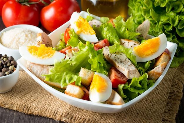 Salada caesar em uma tigela branca na mesa de madeira