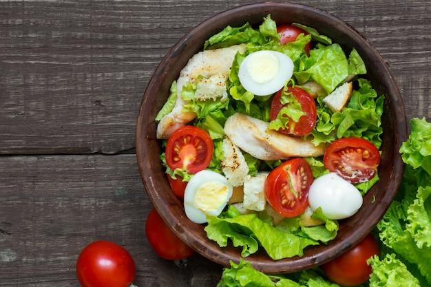 Salada caesar fresca com frango, ovos de codorna, tomate e alface em uma tigela