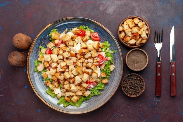 Salada caesar vista de cima com vegetais fatiados e tostas dentro do prato na mesa escura salada de vegetais comida almoço refeição tostas sabor