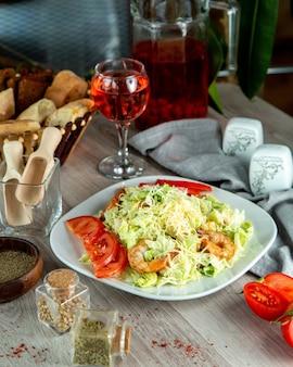 Salada caesar vista frontal com fatias de tomate camarão e um copo de refrigerante