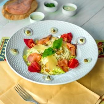Salada caesar vista frontal com peixe vermelho e molhos