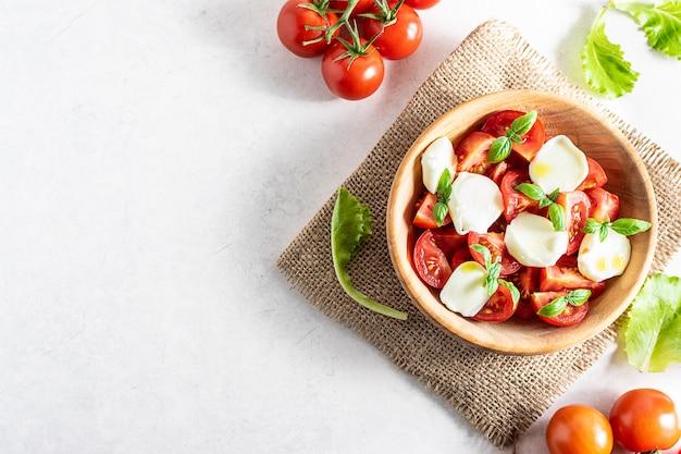 Salada caprese caseira fresca com tomate, manjericão, mussarela e azeite na vista superior da mesa de mármore branco.