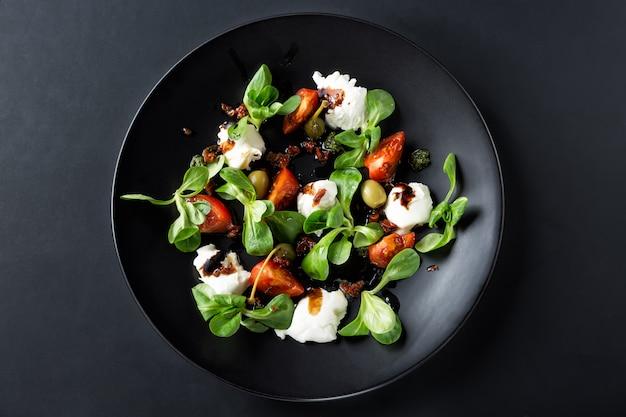 Salada caprese com mussarela, tomate, manjericão e vinagre balsâmico, dispostos em chapa preta