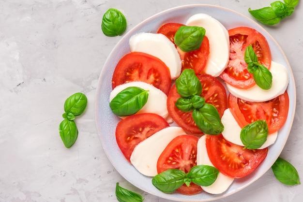 Salada caprese com tomate maduro e queijo mussarela, folhas de manjericão fresco. comida italiana
