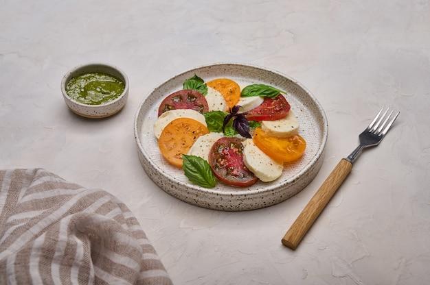 Salada caprese com tomate vermelho e amarelo, manjericão pesto e queijo mussarela em prato branco perto