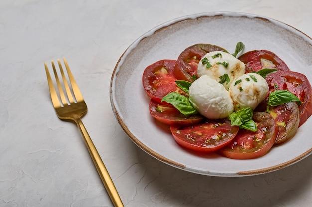 Salada caprese com tomate vermelho, manjericão e queijo mussarela em prato branco e garfo dourado
