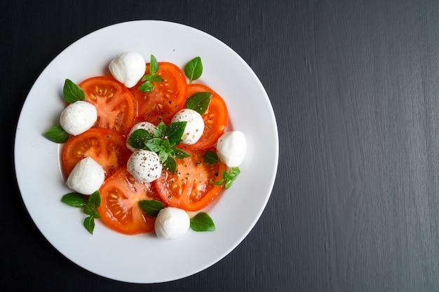 Salada caprese com tomates maduros e mussarela com manjericão fresco folhas. comida italiana.