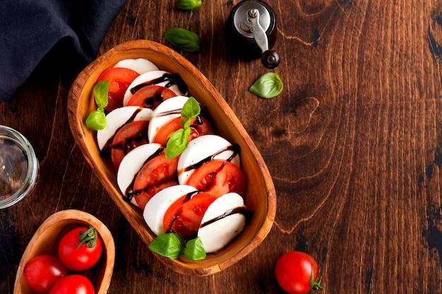 Salada caprese comida italiana com tomates maduros, manjericão fresco de jardim e queijo mussarela em uma tigela de madeira verde-oliva no antigo fundo rústico. vista superior plana lay