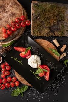 Salada caprese da vista superior. queijo mussarela, tomate e folhas de manjericão na placa preta na madeira