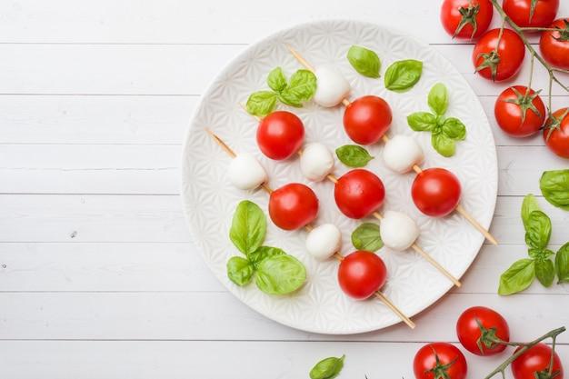 Salada caprese de tomate, queijo mussarela e manjericão em um prato branco. cozinha italiana. espaço da cópia