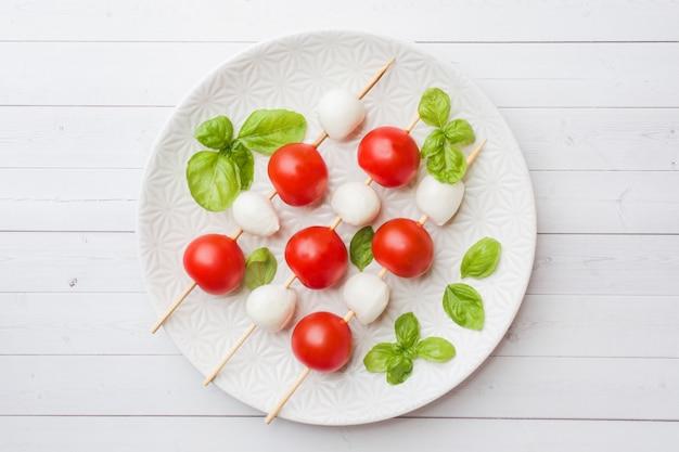 Salada caprese de tomate, queijo mussarela e manjericão em um prato branco. cozinha italiana.