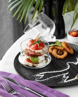 Salada caprese em copo com anéis de cebola
