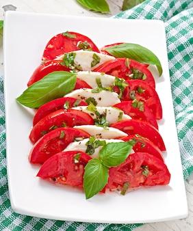 Salada caprese. fatias de tomate e mussarela com folhas de manjericão.
