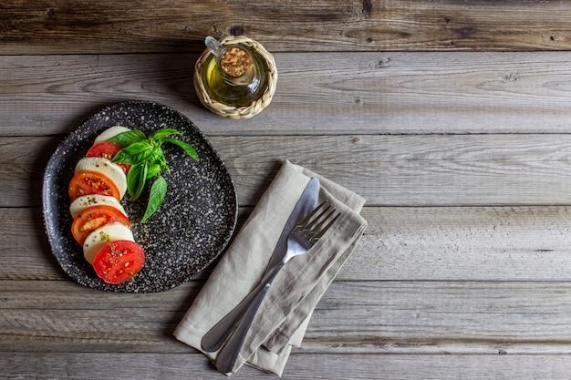 Salada caprese italiana com mussarela e tomates. de madeira. comida saudável.