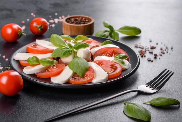 Salada caprese italiana com tomate fatiado, queijo mussarela, manjericão, azeite. servido em prato preto vintage sobre fundo escuro de concreto