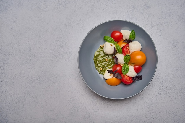 Salada caprese italiana com tomate maduro, manjericão pesto e queijo mussarela em prato fundo cinza