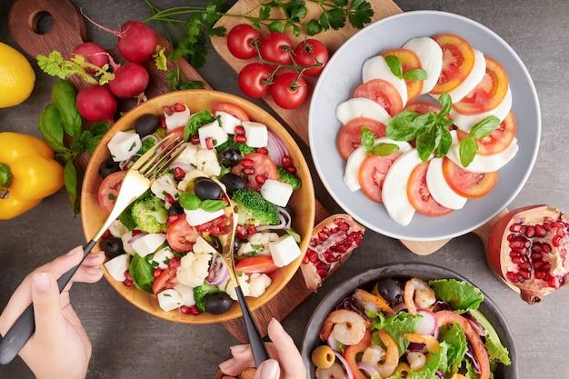 Salada caprese italiana com tomate, manjericão, mussarela, azeitonas e azeite. ingredientes da salada caprese tradicional italiana. mediterrâneo, salada grega, salada de camarão. conceito de comida orgânica e natural.