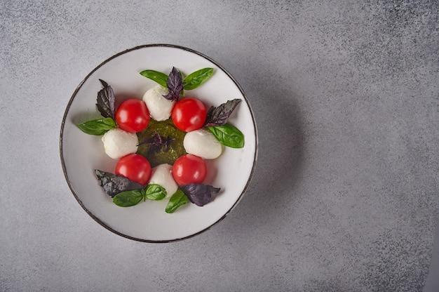 Salada caprese italiana com tomates maduros, manjericão fresco e queijo mussarela em prato branco