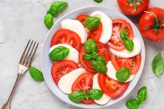Salada caprese italiana fresca com tomate fatiado, queijo mussarela, manjericão, azeite e garfo em um prato