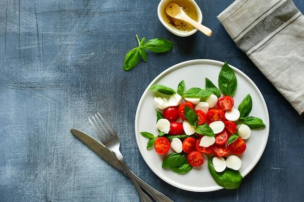 Salada caprese italiana: tomate vermelho, mussarela e manjericão, cozinha italiana. almoço saudável.
