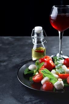 Salada caprese. refeição saudável com tomate cereja, bolas de mussarela e manjericão com vinho tinto