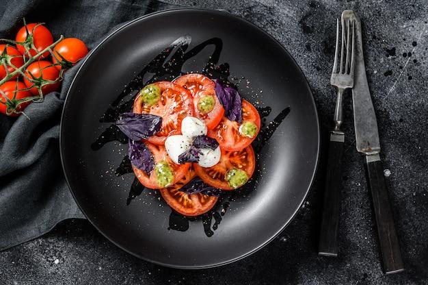 Salada caprese. refeição saudável com tomate cereja, bolas de mussarela e manjericão roxo. conceito para uma refeição vegetariana saborosa e saudável. fundo preto. vista do topo