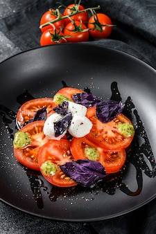 Salada caprese. refeição saudável com tomate cereja, bolas de mussarela e manjericão roxo. vista do topo