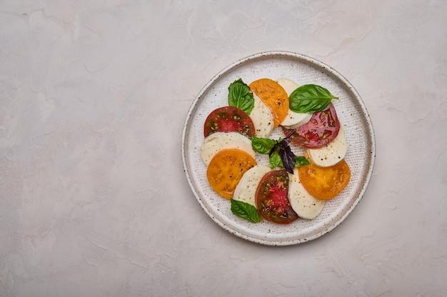 Salada caprese vista de cima com tomate vermelho e amarelo, manjericão fresco e queijo mussarela em prato branco