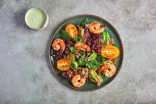 Salada caseira com camarão frito, tomate amarelo, rúcula, espinafre, alface e molho em um prato de cerâmica, vista superior